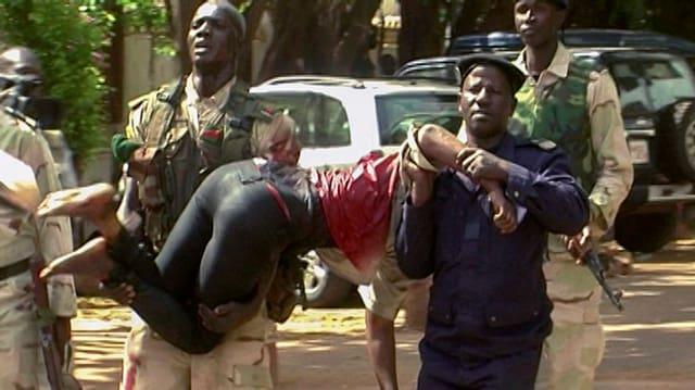 Zwei Soldaten bringen eine verletzte Geisel in Sicherheit.