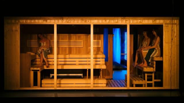 Eine Sauna, vorne offen und der Zuschauer blickt hinein. Darin sitzen drei Frauen mit Tüchern bedeckt.