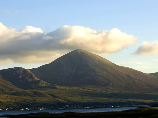 Der Berg Croagh Patrick von weitem, wie er eingebettet von grünen Weisen vor einem See liegt.
