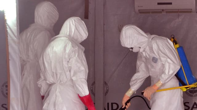 Drei Männer in Schutzanzügen gegen Ebola reinigen ein Zimmer