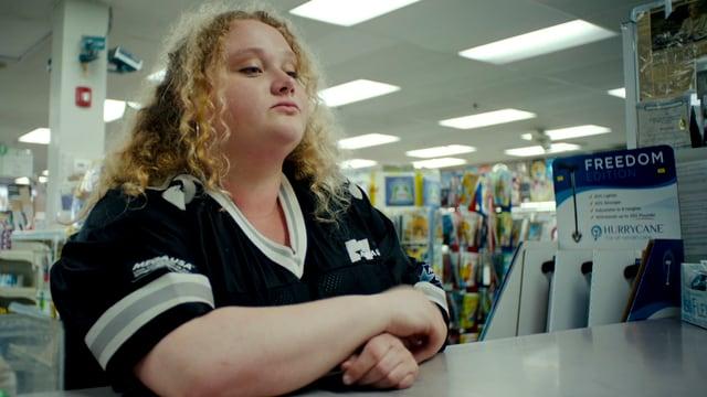 Eine junge, übergewichtige Frau lehnt am Tresen.