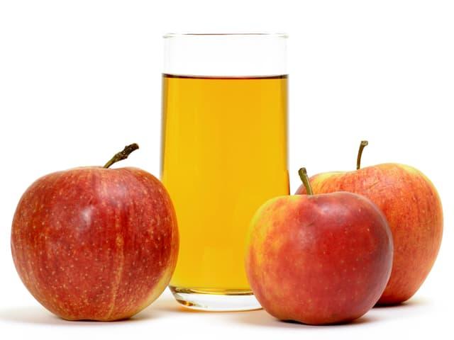 Drei Äpfel und Glas mit Apfelsaft.