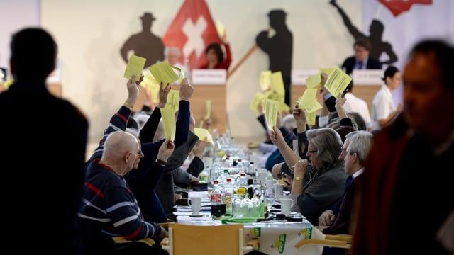 Symbolbild: Die SVP-Delgeierten bei ihrer Versammlung letztes Wochenende; Sie sitzen an langen Tischen und stimmen ab, indem sie ein gelbes Papier in die Höhe strecken.