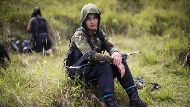 Junge Frau in Tarnkleidung sitzt mit Gewehr auf den Knien im Gras.