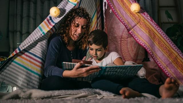 eine Frau liest einem Kind vor, in einem selbstgebauten Zelt