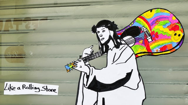 Strassenkunst: Jesus-Figur trägt bunte Gitarre über der Schulter.