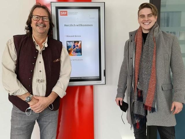 Vincent Gross steht neben Musikredaktor. Auf einem Display im Hintergrund ist ein Bild des Sängers mit der Überschrift «Willkommen» zu sehen.