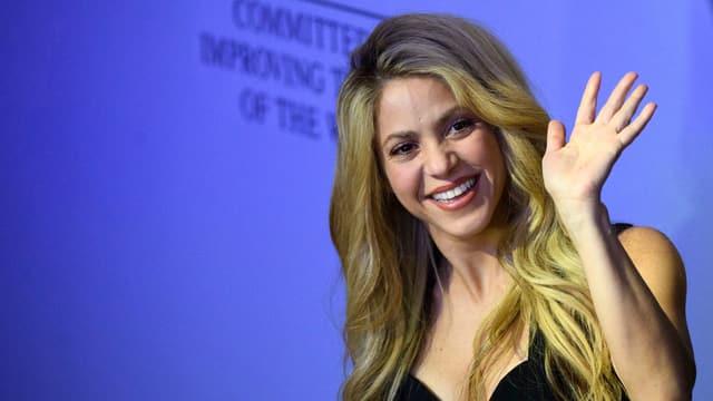 Popstar Shakira, winkend vor blauem Hintergrund.