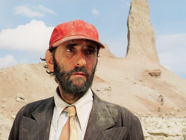 Mann mit roter Kappe in der Wüste.