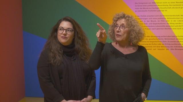 Zwei Frauen vor bunter Wand.