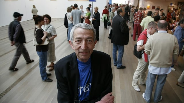 Mann älteren Alters steht im Foyer der Fondation Beyeler in Basel. Hinter ihm tummeln sich Menschen, die eine Ausstellung besuchen wollen.