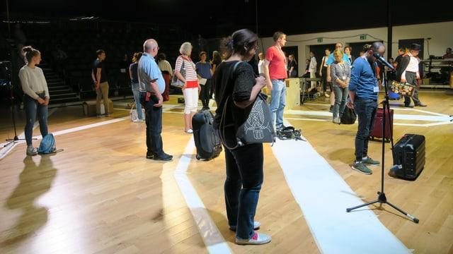 Mit gepackten Koffern stehen mehrere Laienschauspieler auf einer Bühne.