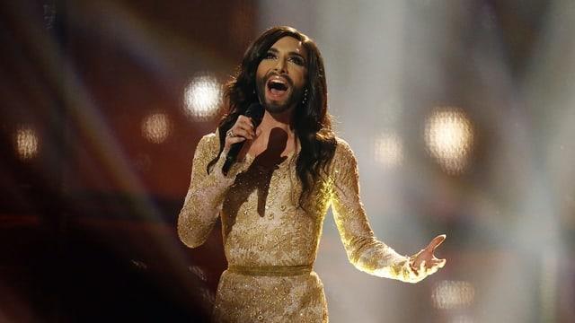 Conchita Wurst mit Bart und langen Haaren und goldenem Kleid.
