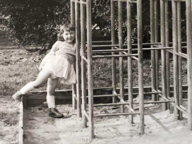 Ein Mädchen lehnt an einem Klettergerüst.