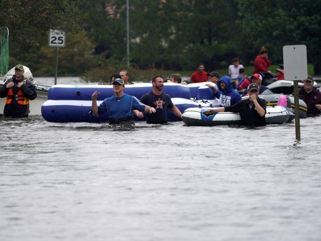 Menschen mit Gummibooten gehen im hüfttiefen Wasser.