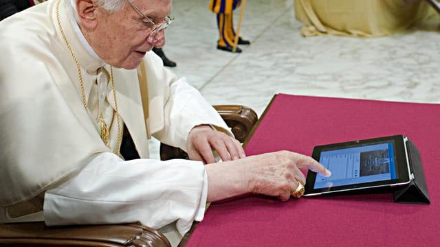 Papst Benedikt XVI. tippt auf einem iPad eine Twitter-Nachricht.