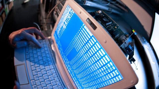 Ein Mann tippt Befehlszeilen in seinen Laptop