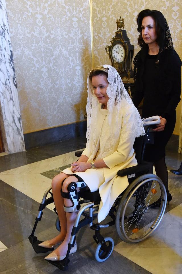 Königin Mathilde wird im Rollstuhl geschoben.