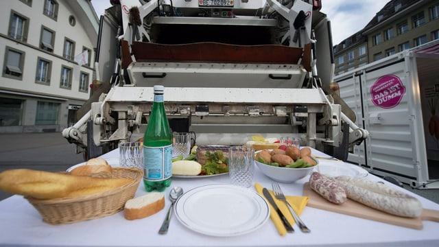 Zu sehen ist ein gedeckter Tisch mit Brot, Wurst, Kartoffeln, Käse, Salat und Wasser. Der Tisch steht in einer von Wohnhäusern gesäumten Strasse vor dem Schlund eines Müll-Wagens.