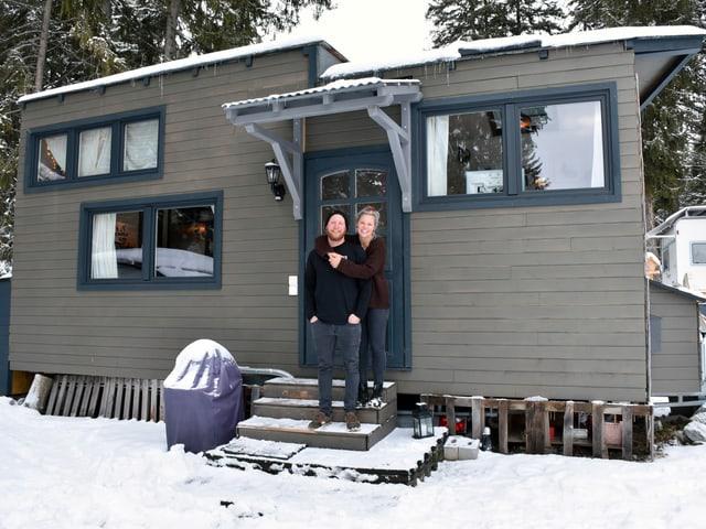 Mann und Frau vor dunklem Haus auf Rädern in weissem Schnee.