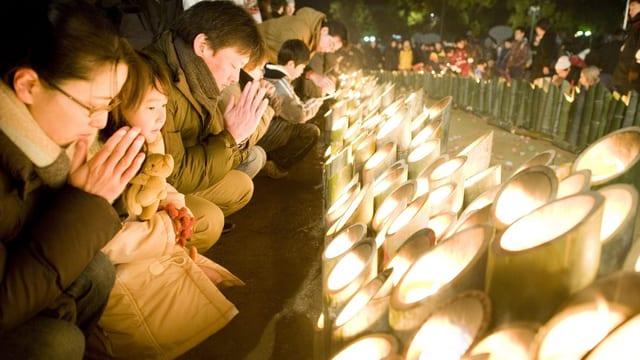 Menschen falten die Hände vor Kerzen.