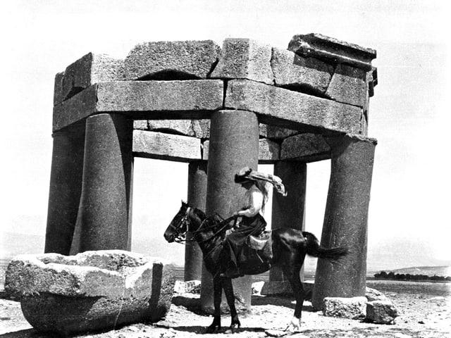 Frau sitzt auf Pferd vor einem Monument auf Stein.