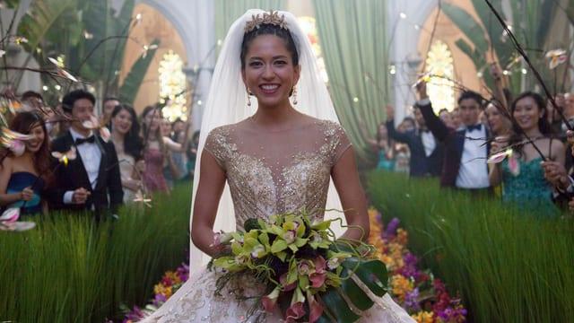 Braut in Glitzerkleid mit Orchideenstrauss. Dahinter Gäste in teuren Roben.