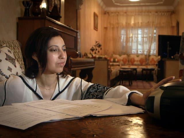 Sanae el Amri sitzt vor den neu aufgeschriebenen Noten und überlegt als Vorbereitung auf die Probe einheitliche Verzierungen für den ganzen Chor.