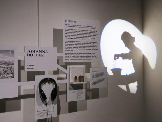 Texttafeln einer Ausstellung, dazu ein Kopfhörer und die Umrisse einer Frauengestalt, die auf eine Wand projiziert wird.