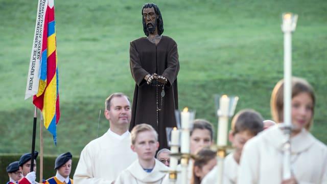Ein Festgottesdienst zu Ehren von Niklaus von Flue. Gläubige tragen eine Statue von Bruder Klaus.