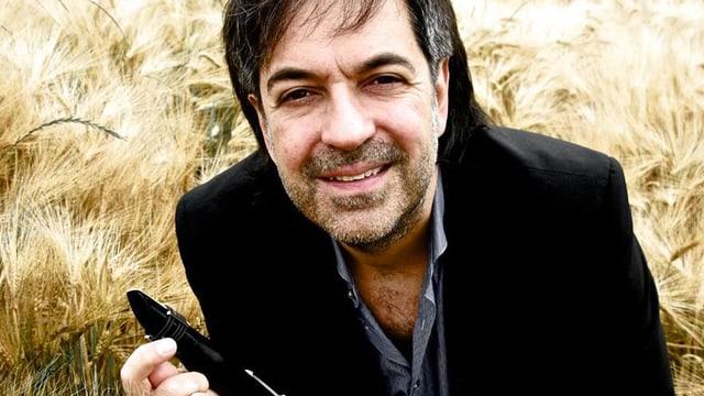 Marco Santilli liegt in einem Feld mit seiner Klarinette.