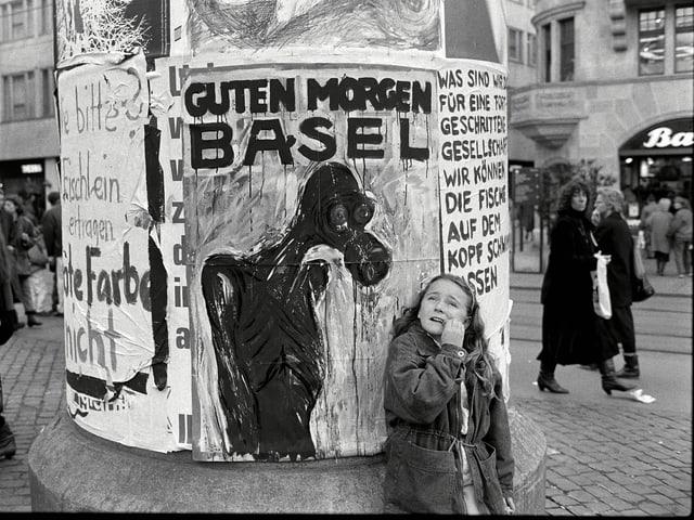 Ein Mädchen sitzt vor einem Plakat.