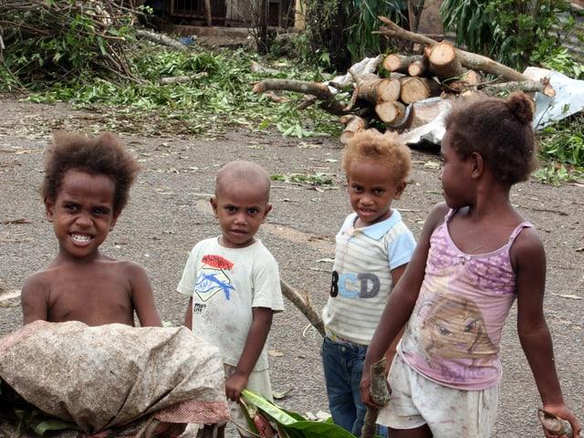 Kinder stehen mit gesammeltem Brennholz auf der Strasse.