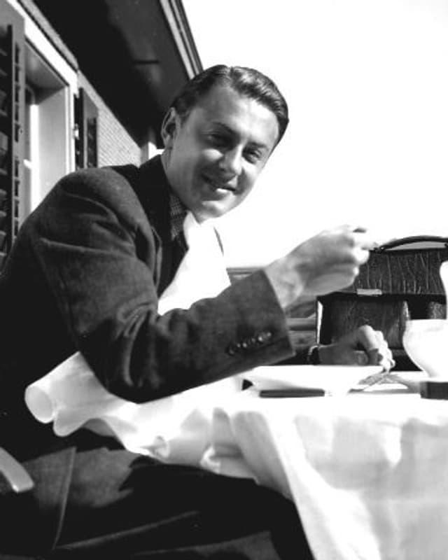 Artur Beul sitzt draussen vor einem Chalet an einem Tisch. Er ist hübsch frisiert und trinkt eine Tasse Kaffee.