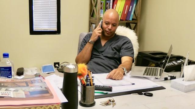 Klinik-Direktor Dalton Johnson hinter seinem Schreibtisch