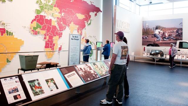 Zwei Leute im Museum. Sie stehen vor einer grossen Weltkarte.
