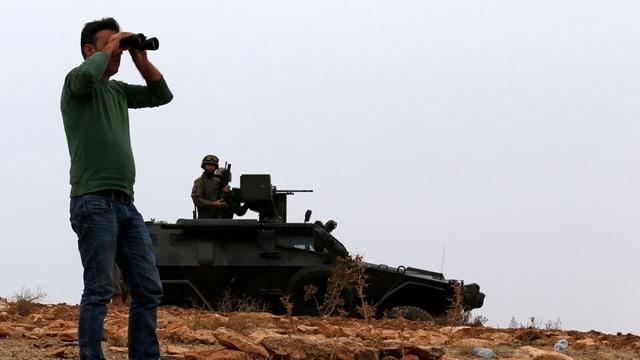Mann beobachtet vor Panzer mit Fernglas