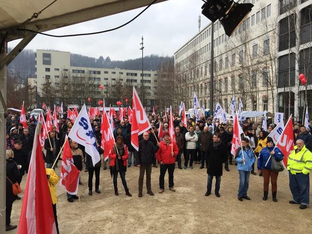 Mehrere Menschen demonstrieren mit Fahnen.
