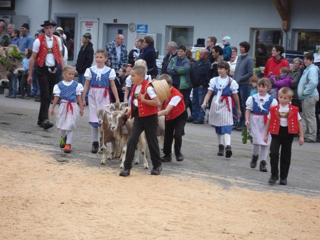 Mädchen und Buben in Trachten ziehen mit ein paar Ziegen durchs Dorf.
