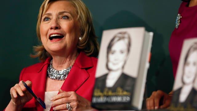 Clinton lachend mit einem Buch im Vordergrund.