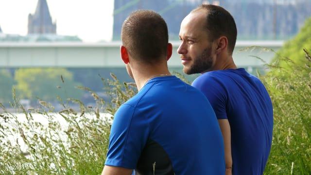 Zwei Männer, beide in blauen T-Shirts, sitzen im Gras an einem Fluss und unterhalten sich lachend.