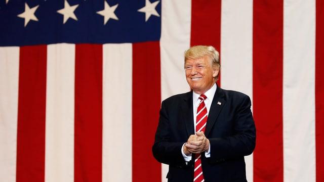 Donald Trump steht vor der US-Flagge.