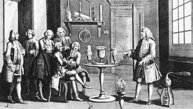 Die schwarz-weisse Abbildung eines Raumes, in dem Studenten und ein Lehrer um einen Tisch mit allerlei Utensilien stehen und sitzen.
