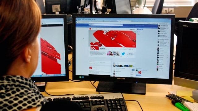 Eine Journalistin sitzt vor zwei Bildschirmen im Newsroom von SRF.