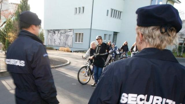 Zwei Personen in Securitas-Uniformen stehen vor einem Haus. Im Hintergrund einige Jugenliche auf ihren Fahrrädern