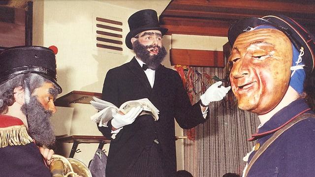 Szene in einem Schwarzenburger Wirtschaus anlässlich des Silvesterbrauchs «Altjahrsesu». Maskierte stellen Altjahrspfarrer, Anführer und Briefträger dar.
