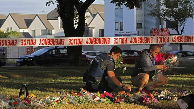 Zwei Polizisten heben Blumen hoch, die vor der Moschee in Christchurch niedergelegt wurden, nachdem dort das Attentat geschah.