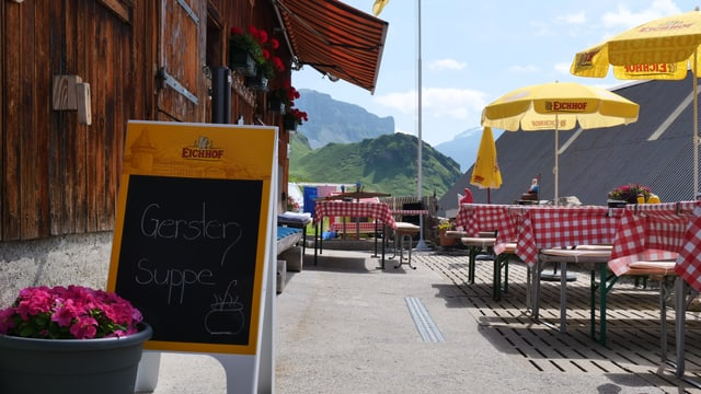 Eine kleine Wirtschaft in den Bergen mit Tischen auf der Terrasse. Daneben stehen gelbe Sonnenschirme.