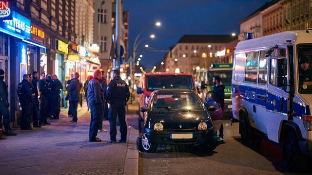 Szene vor einem Lokal mit Polizeiautos und Ordnungsleuten.