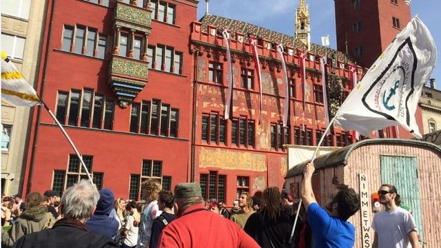 Fahnen werden geschwingt, im Hinergrund Rathaus